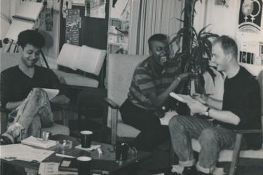 Keith Trotman, Colleen Humphrey and Jamie McCarthy working at the Greenwich Lesbian and Gay Centre, sitting at a coffee table, smiling and laughing