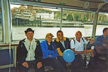 Four adults and a child sitting on the Pride Boat sailing past the Globe Theatre towards Westminster, 1998