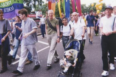 Three Metro Centre Pride participants featured as marchers in the parade with a child in a pushchair.
