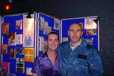 Two people standing in front of their HIV and sexual health outreach stall at the Long Yang club night, 1999