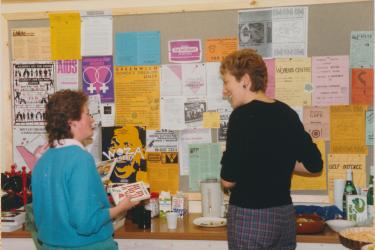 Two people talking in front of the Greenwich Lesbian and Gay Centre community information noticeboard in 1986