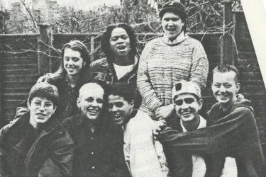 A group of eight young people smiling, hugging and laughing in a posed photograph for participants in the Young Women's Video Project