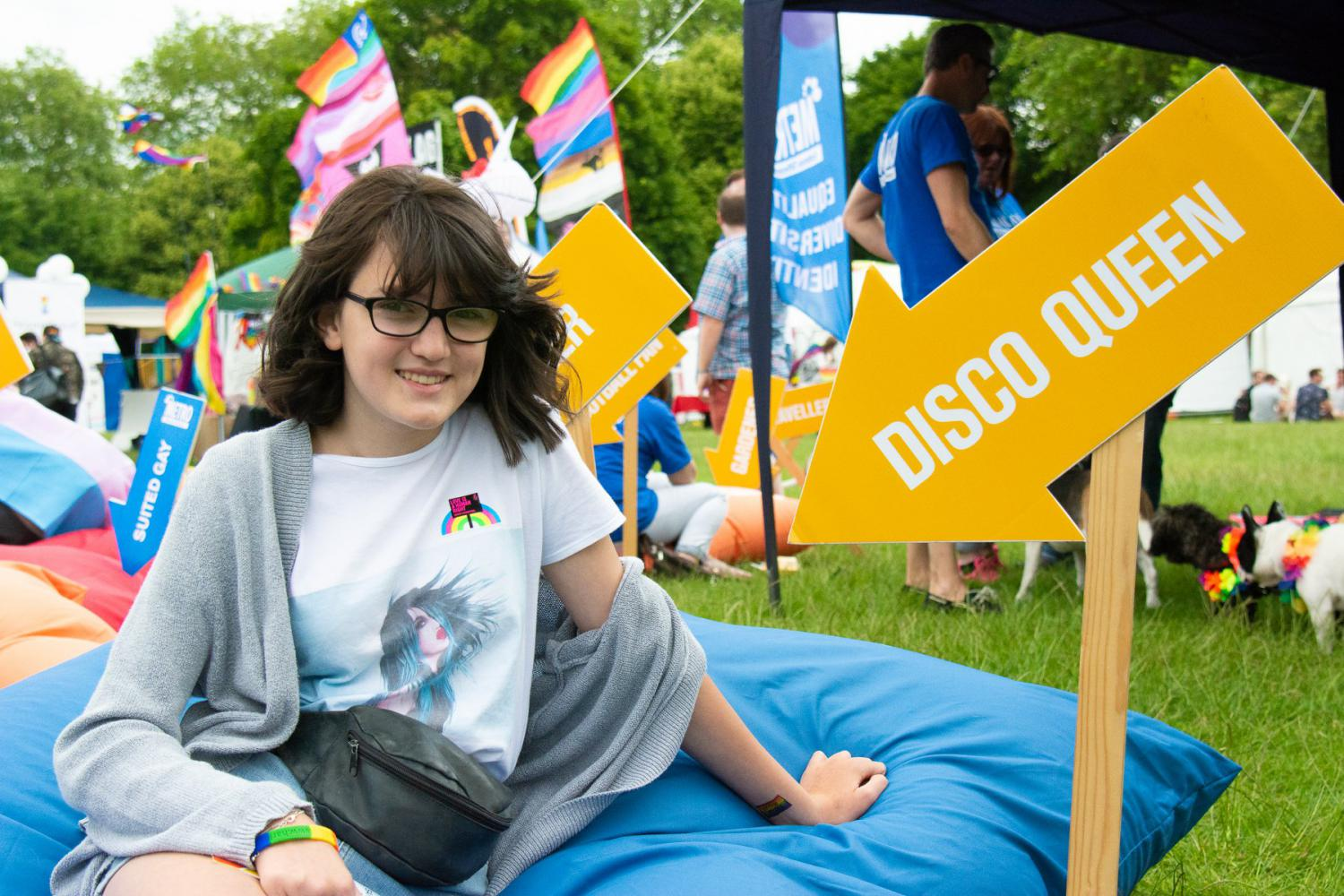 A young person with a disco queen arrow in front of the METRO stall at Essex Pride