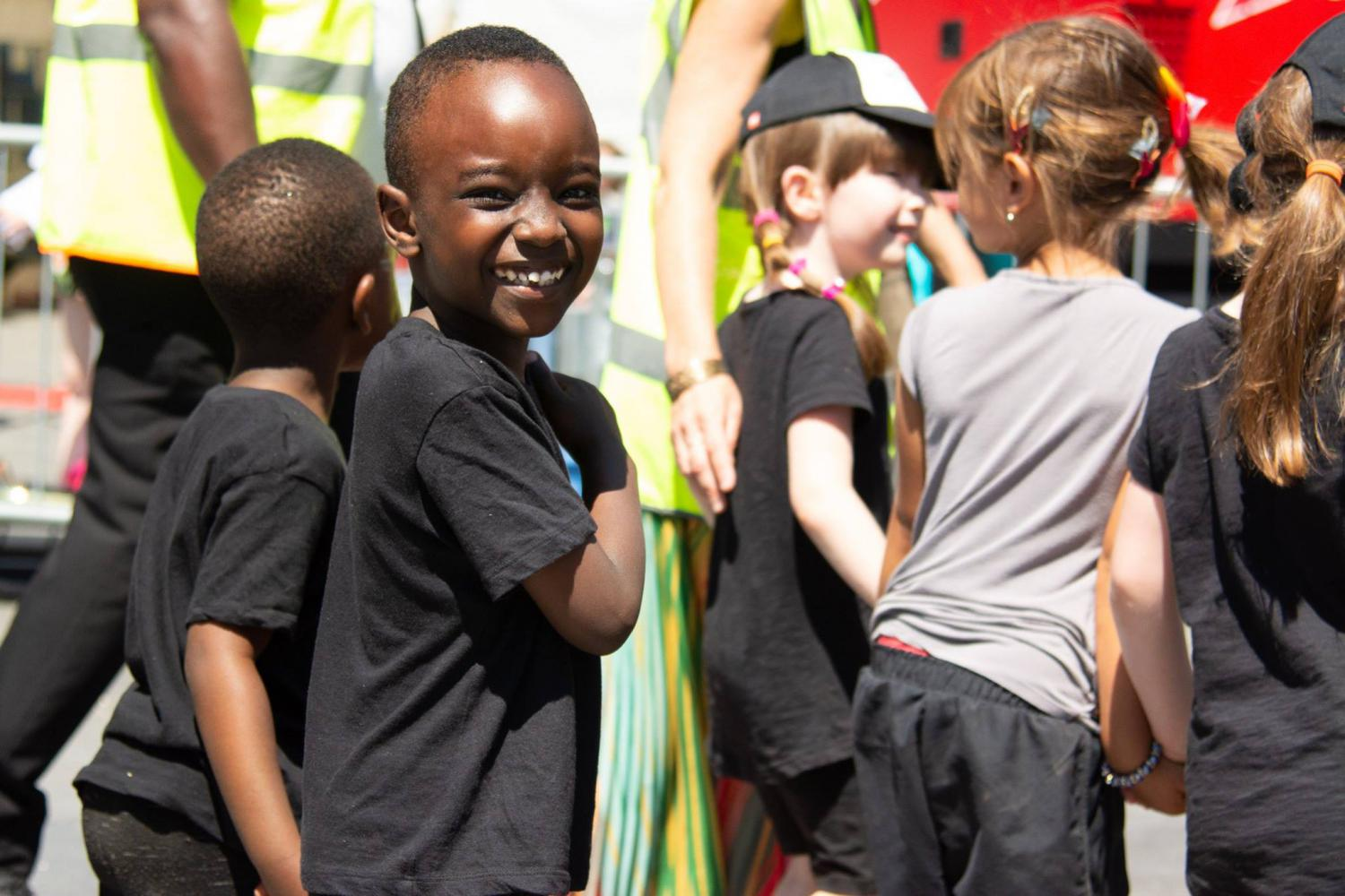 A boy wearing a black t-shirt smiles in the parade at the Greenwich Get Together
