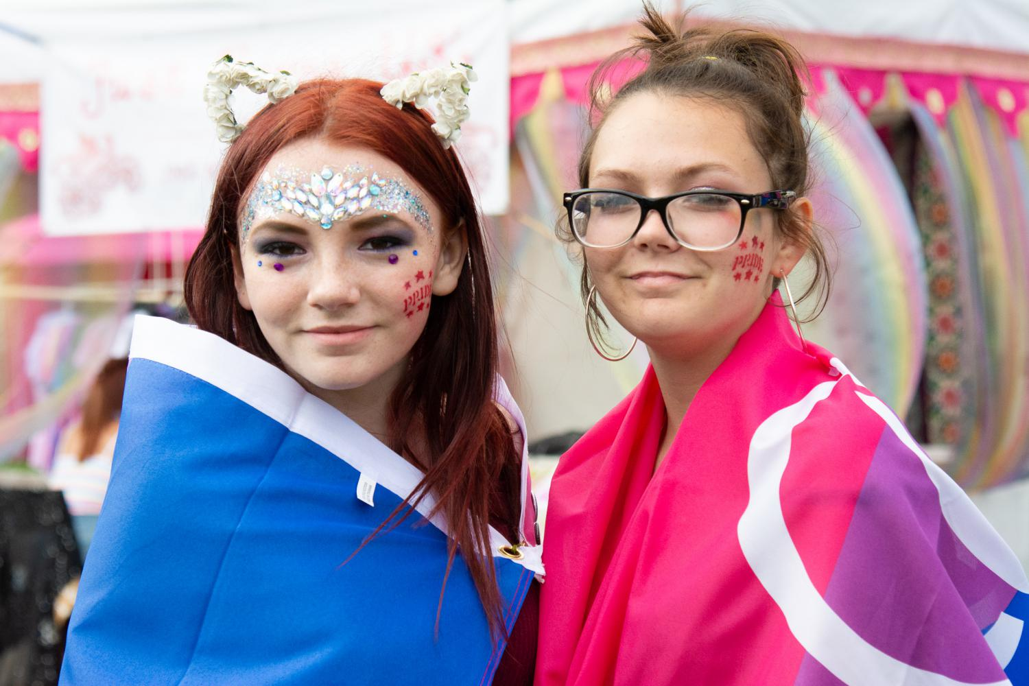 Two young people wearing bisexual flags at Essex Pride