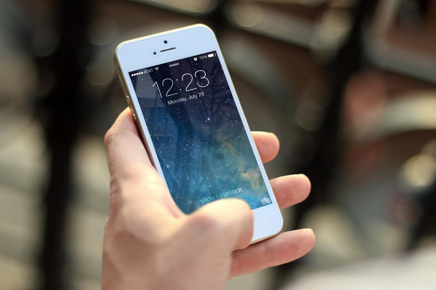 A hand holding a white iPhone with bokeh in the background