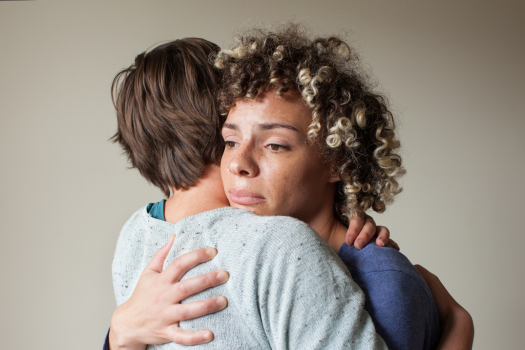 Woman looking anxious and hugging another person