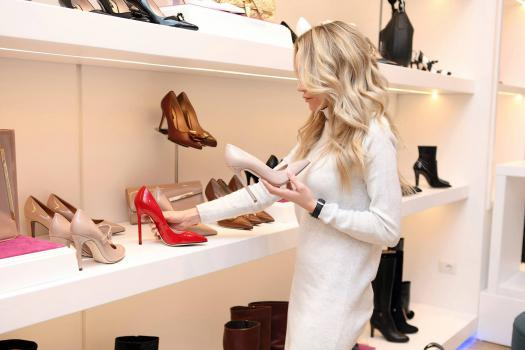 A woman in a shoe shop holding a pair of high heels