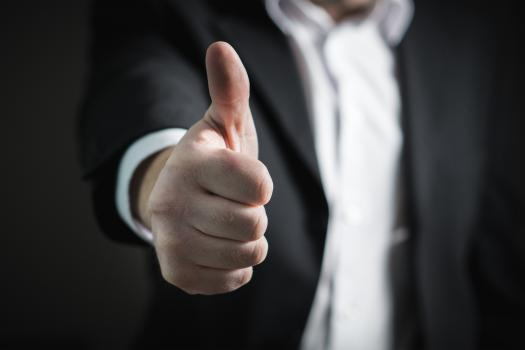 Man in a suit doing a thumbs up gesture