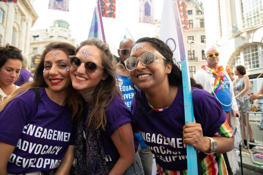Three people wearing purple METRO community t-shirts at Pride in London