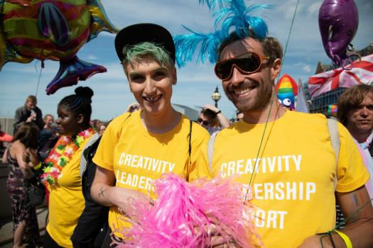 A young person with green hair in a yellow METRO t-shirt with Dan Baker at Margate Pride