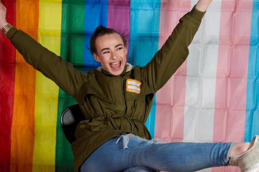 A young person wearing makeup in front of a trans flag at the METRO youth summit in Southwark