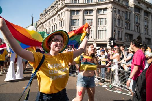 A young person holding a rainbow flag and wearing a yellow METRO t-shirt at Pride in London