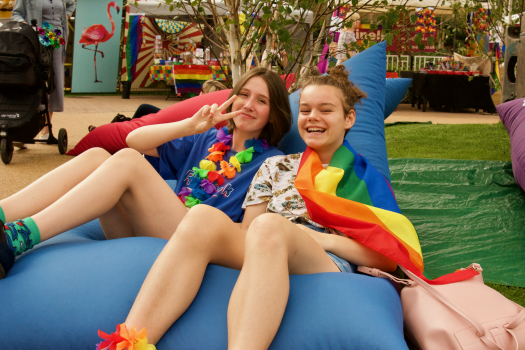 Two young people, one wearing a rainbow flag, sitting on a blue METRO beanbag