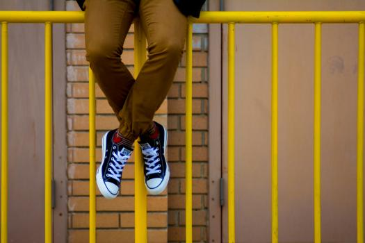 A young man sitting on yellow railings wearing sneakers