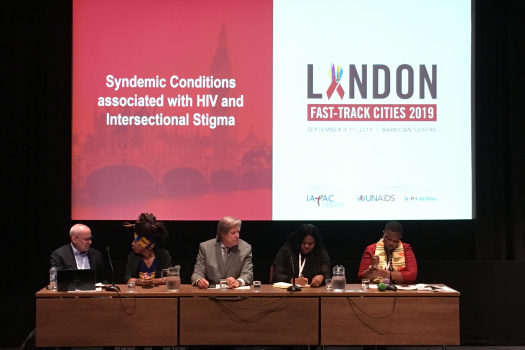 Panel of five in front of title slide, 'Syndemic conditions associated with HIV and Intersectional Stigma