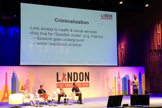 Slide on Criminalisation above panel and speaker on stage at London Fast-Track Cities Conference