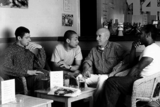 Four men sitting talking around a coffee table in a posed photograph to promote the Metro Thrust HIV prevention and sexual health outreach project, 1995