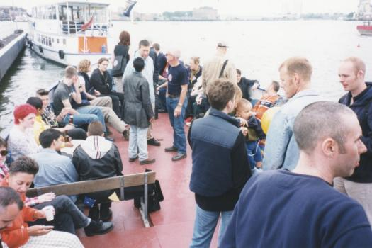 Groups of people talking on the Pride Boat from Greenwich to Westminster in 1998