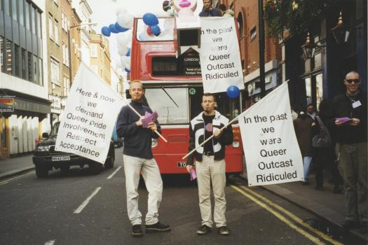Two men standing in front of a red London Bus decked out for The Metro Centre's Ship of Fools-themed participation in World Mental Health Day, 1998