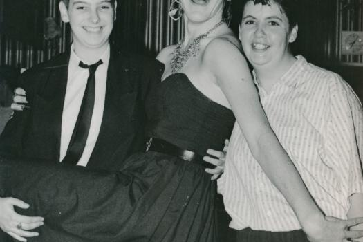 Three members of the Greenwich Lesbian and Gay Centre celebrating and posing at a 21st birthday party, 1989