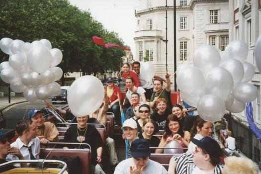 Young people with balloons on the top deck of The Metro Centre bus