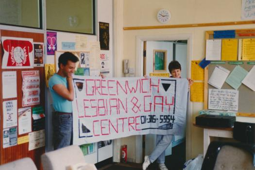 Two workers from the Greenwich Lesbian and Gay Centre holding up the organisation's banner in the Centre, 1989