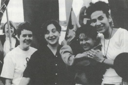 Group of four women smiling and hugging on board The Metro Centre's Greenwich Faerie boat to Pride, 1995