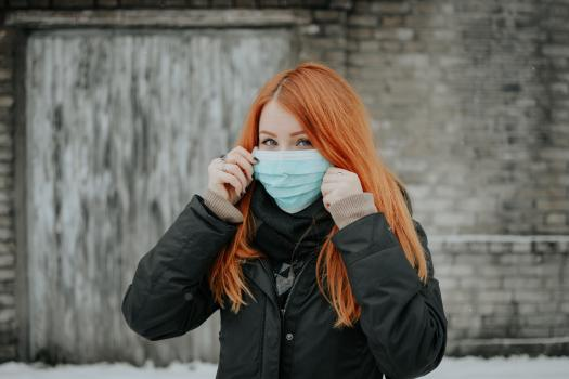 Red haired woman holding up a face mask