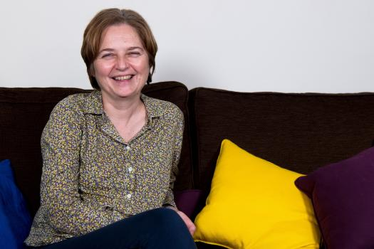Photo of Helen on a sofa with colourful cushions