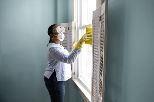 Asian woman in face mask cleaning window