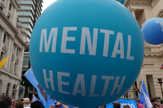 Photo of a very large teal coloured balloon in the street with the words Mental Health written across it